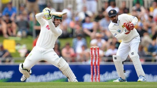 Australian batsman Phil Hughes (L) cuts a ball during the first day of the first Test in Hobart on December 14, 2012