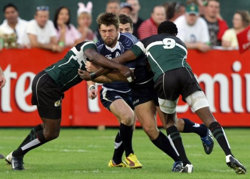 David Tait (C) fends off several Zimbabwe players at the IRB World Sevens Series in Dubai on December 4, 2009