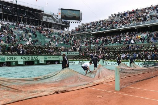 Staff remove the covers from Centre Court at Roland Garros on June 8, 2012