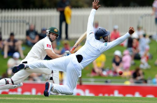Sri Lanka's Dimuth Karunaratne (R) attempts a catch by Australia's Matthew Wade, in Hobart, on December 15, 2012