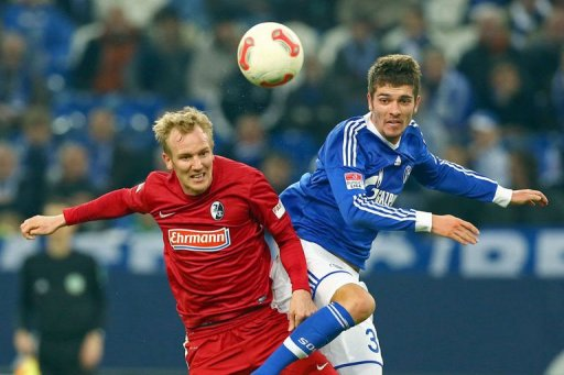 Freiburg's Jan Rosenthal (L) and Schalke's Roman Neustaedter fight for the ball on December 15, 2012
