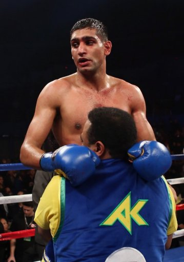 Amir Khan celebrates his victory over Carlos Molina, on December 15, 2012