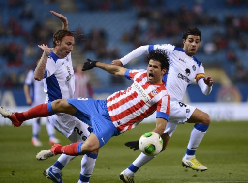 Atletico Madrid's Diego da Silva Costa (C) fights for the ball with Getafe's players, on December 12, 2012