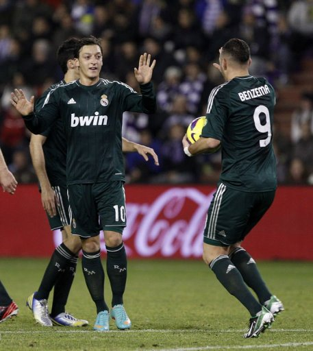 Real Madrid's Mesut Ozil (L) celebrates scoring a goal against Real Valladolid, on December 8, 2012