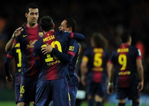 Barcelona's forward Lionel Messi (C) celebrates with midfielder Sergio Busquets (L) and defender Adriano (R)