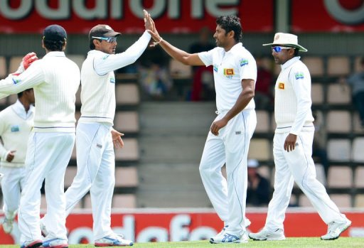 Sri Lanka's Chanaka Welegedara (2/R) is congratulated by teammates after taking a wicket on December 17, 2012