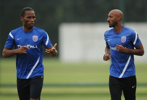 Shanghai Shenhua players Didier Drogba (L) and Nicolas Anelka warm up during a training session on July 16, 2012