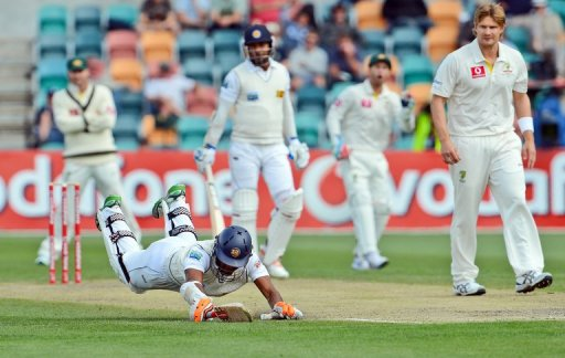 Sri Lanka batsman Dimuth Karunaratne dives to beat a throw at the wicket in Hobart on December 17, 2012