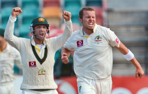 Australia's Peter Siddle (R) celebrates with Phil Hughes after dismissing Thilan Samaraweera on December 18, 2012