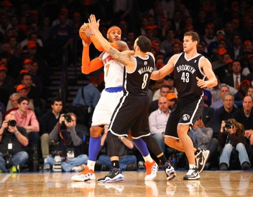 Carmelo Anthony (L) is blocked by the Nets' Deron Williams (C) and Kris Humphries during their game on December 19, 2012