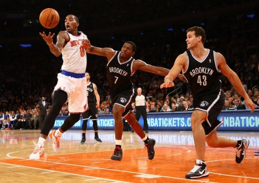 The Knicks' J.R. Smith (L) grabs a rebound as the Nets' Joe Johnson (C) defends during their game on December 19, 2012