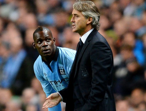 Manchester City manager Roberto Mancini (R) speaks to striker Mario Balotelli during a match on October 3, 2012