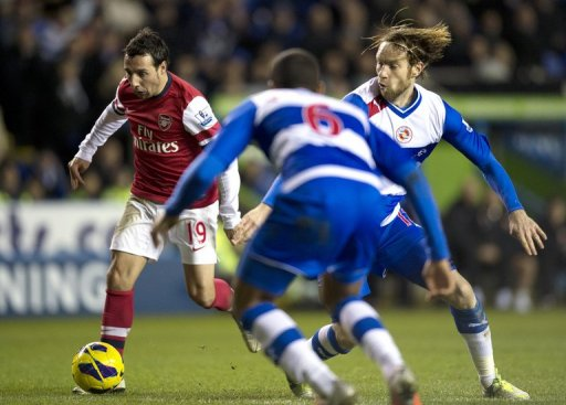 Arsenal's Santi Cazorla (L) fights for the ball with Reading's Kaspars Gorkss (R), in Reading, on December 17, 2012