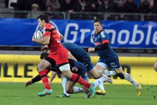 Grenoble's fly-half Valentin Courrent (R) runs in Grenoble on December 22, 2012
