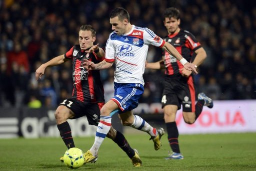 Lyon's forward Anthony Reveillere (C) fights for the ball with Nice's forward Eric Bautheac in Lyon on December 22, 2012
