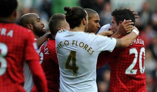 Swansea's Ashley Williams (2nd right) and Manchester United's Robin van Persie clash in Swansea on December 23, 2012