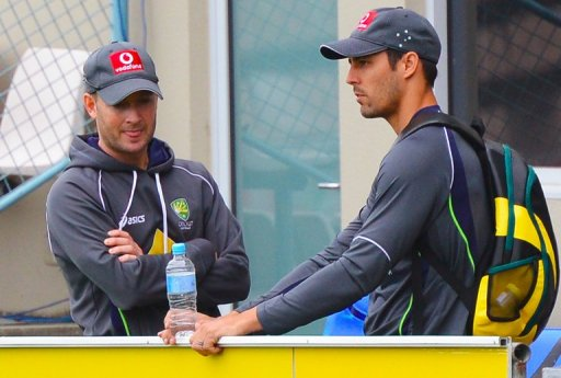 Michael Clarke (L) speaks with Mitchell Johnson during a training session in Hobart, on December 13, 2012
