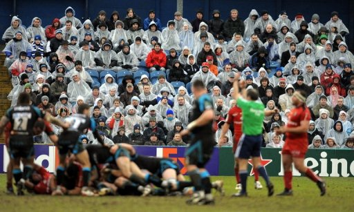 Fans watch in the rain as the Sale Sharks play Toulouse in Stockport, England on January 24, 2010