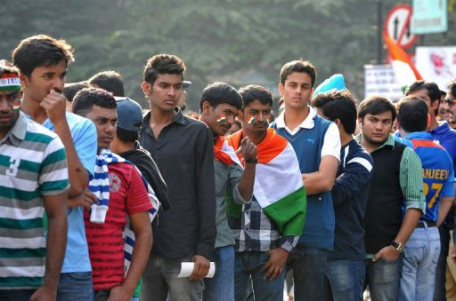Indian cricket fans wait in line outside The M. Chinnaswamy Stadium in Bangalore on December 25, 2012
