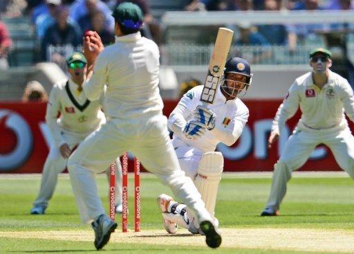 Kumar Sangakkara drives a ball at Australian fielder Ed Cowan (2nd L) in the second Test on December 26, 2012