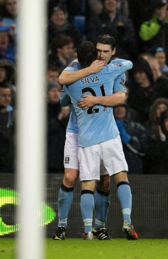 City midfielder Gareth Barry celebrates with David Silva after scoring his injury-time winner on December 22, 2012