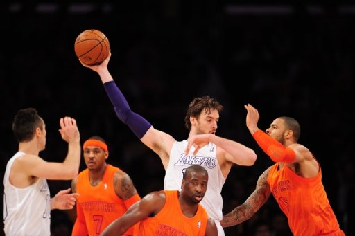 Pau Gasol (C) of the Los Angeles Lakers grabs the ball against the New York Knicks on December 25, 2012