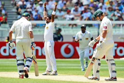 Dhammika Prasad celebrates dismissing Shane Watson (R) on the second day of the second Test on December 27, 2012