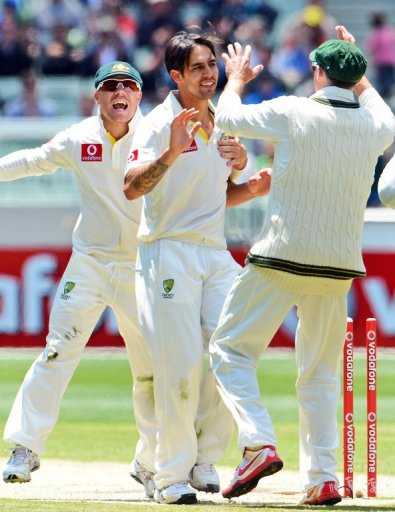 Australia's Mitchell Johnson (C) is congratulated by David Warner (L) and Michael Hussey, on December 28, 2012
