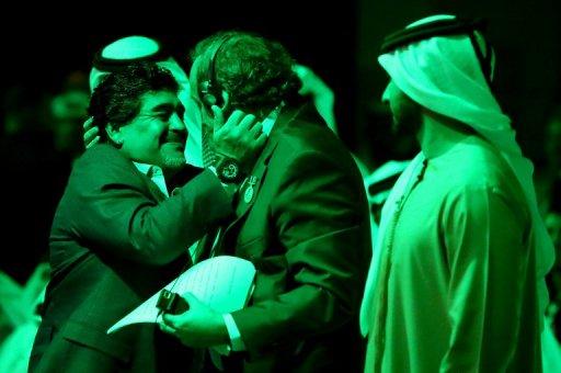 Michel Platini (C) hugs Diego Maradona (L) in Dubai on December 28, 2012