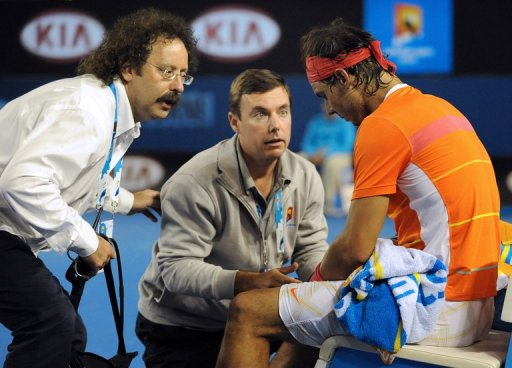 Courtside trainers attend to Rafael Nadal's knee injury during the Australian Open, in Melbourne, on January 26, 2010