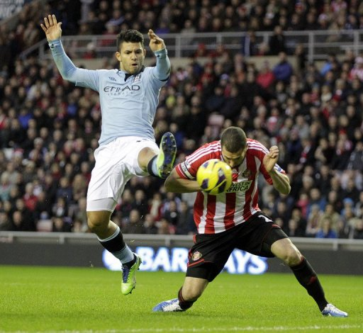 Sunderland's Carlos Cuellar (R) fights for the ball with Manchester City's Sergio Aguero, on December 26, 2012