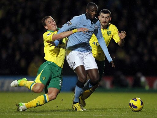 Norwich City's defender Steven Whittaker falls to the ground as he challenges Manchester City's midfielder Yaya Toure