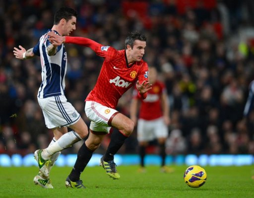 Manchester United's Robin van Persie slips past West Bromwich's  Liam Ridgewell at Old Trafford, December 29, 2012