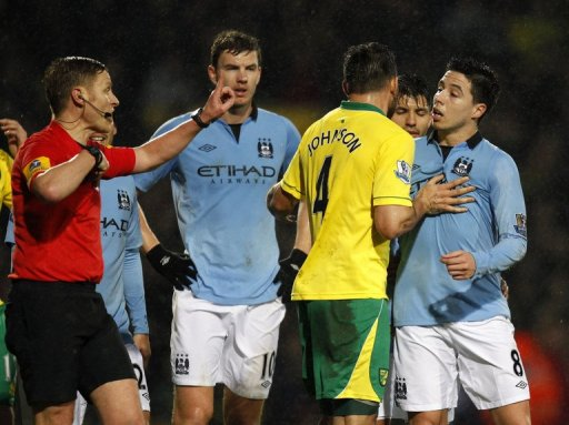 Manchester City's  Samir Nasri (R) is sent off by referee Mike Jones (L) at Carrow Road, December 29, 2012