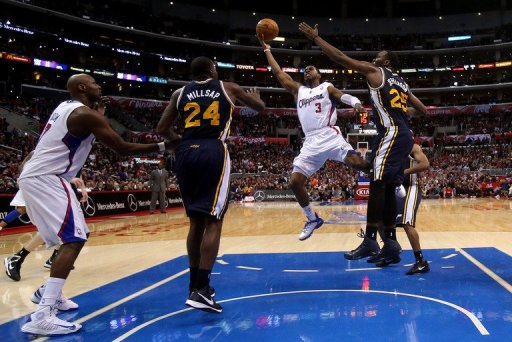 Chris Paul (C) of the L.A. Clippers shoots between Paul Milsap and Al Jefferson of the Utah Jazz, on December 30, 2012