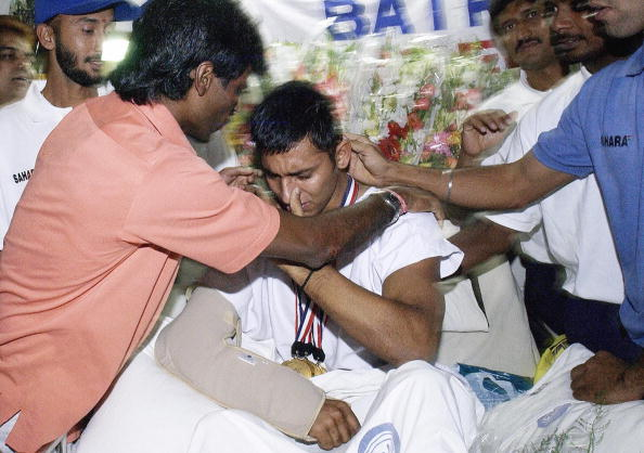 India's national hockey team captain Dhanraj Pillay (L) greets tearful injured penalty-corner specialist Jugraj Singh (C), 30 September 2003, at a hospital in New Delhi following India's win against Pakistan in the Asia Cup field hockey final.  The team paid tribute and shared their trophy with their injured teammate upon their return from Kuala Lumpur to the Indian capital following their Sunday's 4-2 triumph, after Singh suffered multiple injuries in a car crash.