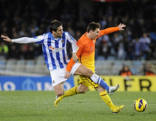 Barcelona's Lionel Messi (R) clashes with Real Sociedad's Markel Bergara in San Sebastian on January 19, 2013