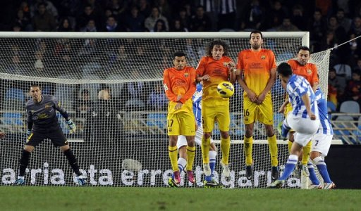 Real Sociedad's midfielder Gonzalo Castro (2nd R) shoots against Barcelona's defence on January 19, 2013