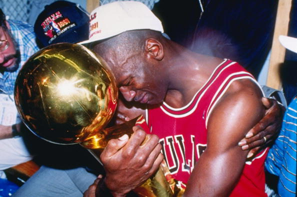 INGLEWOOD, CA - JUNE 12: Guard Michael Jordan #23 of the Chicago Bulls sits nexts to his wife Juanita and his dad James while hugging the NBA Championship Trophy after the Bulls defeated the Los Angeles Lakers 4-1 after Game 5 of the NBA Finals on June 12, 1991 at the Great Western Forum in Inglewood, California.