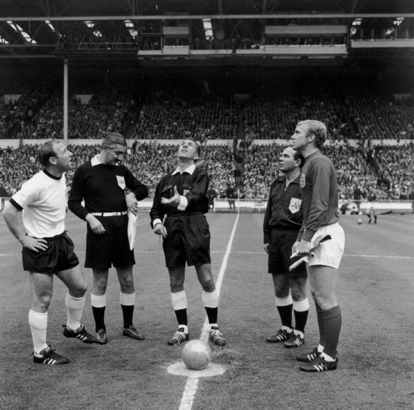 Referee Gottfried Dienst, of Switzerland, tosses the coin before the start of the World Cup final at Wembley between England and West Germany.  He is watched by German captain Uwe Seeler, (left), the Russian linesman Tofik Bakhramov (looking at watch) and English captain Bobby Moore (1941 - 1993) (right).