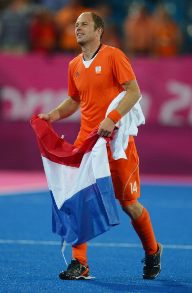 LONDON, ENGLAND - AUGUST 09:  Teun De Nooijer of Netherlands celebrates with his national flag at the end of the Men's Hockey Semi Final match between Netherlands and Great Britain on Day 13 of the London 2012 Olympic Games at Riverbank Arena Hockey Centre on August 9, 2012 in London, England.  (Photo by Lars Baron/Getty Images)