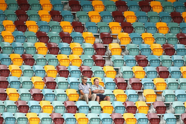 BRISBANE, AUSTRALIA - NOVEMBER 12:  Members of the crowd sit amongst empty seats in the grandstand during day four of the First Test match between Australia and South Africa at The Gabba on November 12, 2012 in Brisbane, Australia.  (Photo by Mark Kolbe/Getty Images)