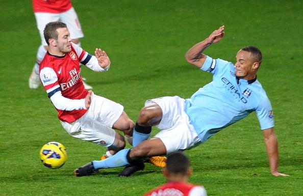 Vincent Kompany challenges Arsenal's Jack Wilshere