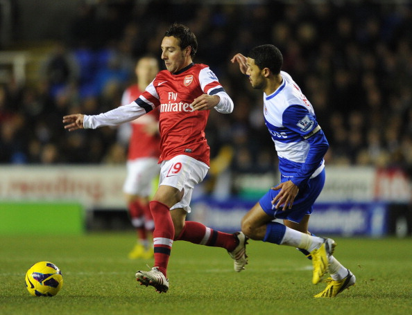 READING, ENGLAND - DECEMBER 17: Santi Cazorla of Arsenal is closed down by Jobi McAnuff of Reading during the Barclays Premier League match between Reading and Arsenal at Madejski Stadium