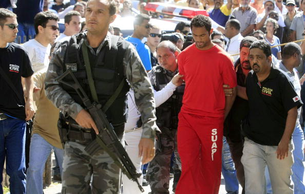 Brazilian footballer Bruno Fernandes de Souza (in red) is taken under custody to the presidium of Belo Horizonte, Brazil.