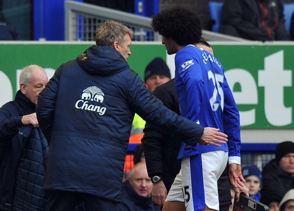 Everton's Scottish manager David Moyes (L) greets Everton's Belgian midfielder Marouane Fellaini (R) as he leaves the field after being substituted during the English FA Cup quarter-final football match between Everton and Wigan Athletic at Goodison Park. Fellaini was booed off the pitch.