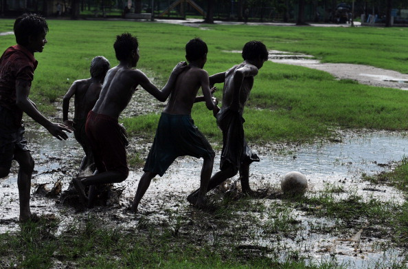 Young Indian slum-dwellers play a game of football on water logged grounds in Kolkata in the monsoons