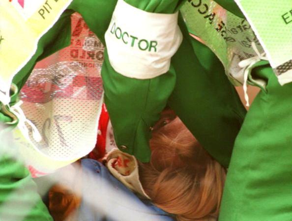 Finnish Formula One driver Mika Hakkinen (C) receives treatment for his crash