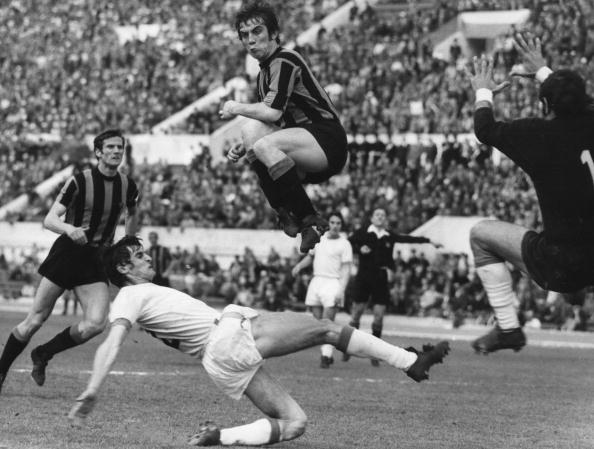 Inter Milan centre-forward Pino Boninsegna leaps high over Lazio's Giorgio Papadopulo during their match at the Olympic Stadium in Rome. On the left is Inter Milan's Giacinto Facchetti.