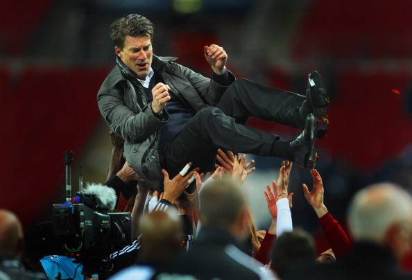 LONDON, ENGLAND - FEBRUARY 24: Swansea players lift up Manager of Swansea City Michael Laudrup after their 5-0 victory in the the Capital One Cup Final match between Bradford City and Swansea City at Wembley Stadium
